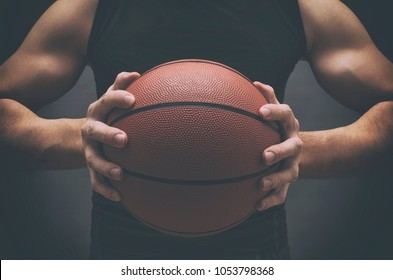 Male basketball player with a ball over dark background. Fit young man in sportswear holding basketball.