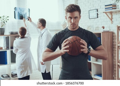 Male basketball player stands in the office of the doctor. Two doctors in the background look at x rays while standing in the office.