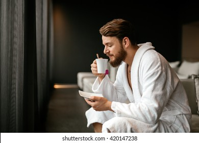 Male in bathrobe relaxing while drinking tea