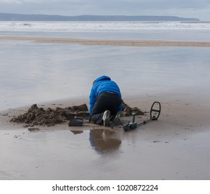 Male Beach Combing for Treasure with a Metal Detector on Westwood Ho Beach with the Atlantic Ocean in the Background on the North Coast of Devon, England, UK