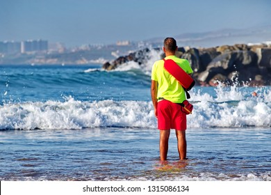 Male in beach lifeguard uniform stands in the water and oversees order and the safety