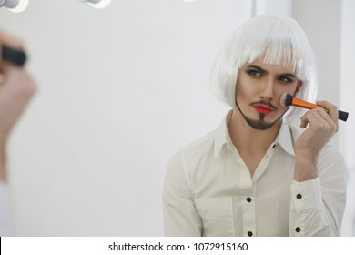 A male beauty blogger looking at his reflection in the mirror while applyng makeup with a thick brush. The femining guy wearing a neat goatee, lipstick, green eyeshadow, silver bob wig, neck tattoo.