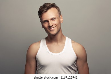 Male beauty, boy next door concept. Portrait of smiling 30-year-old man standing over gray background. Close up. Copy-space. Classic style. Wavy glossy blond hair. Studio shot