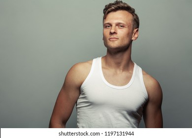 Male beauty, boy next door concept. Portrait of proud smiling 30-year-old man standing over gray background. Close up. Copy-space. Sportsman style. Wavy glossy blond hair. Studio shot