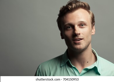 Male beauty, boy next door concept. Portrait of smiling 30-year-old man standing over gray background. Close up. Classic style. Wavy glossy blond hair. Copy-space. Studio shot