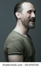 Male beauty concept. Fabulous at any age. Portrait of 40-year-old man laughing over dark gray background. Hair brushed back. Rocker, biker style. Close up. Studio shot