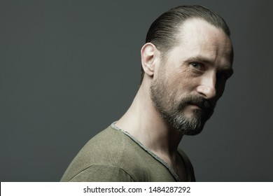Male beauty concept. Fabulous at any age. Portrait of 45-year-old man standing over dark gray background. Hair brushed back. Rocker, biker style. Scar on forehead. Close up. Copy-space. Studio shot