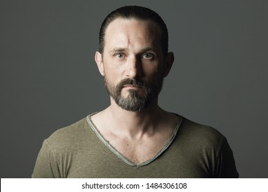 Male beauty concept. Fabulous at any age. Portrait of 45-year-old man standing over dark gray background. Hair brushed back. Rocker, biker style. Scar on forehead. Close up. Text space. Studio shot