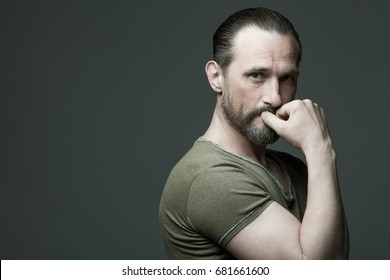 Male beauty concept. Fabulous at any age. Portrait of 40-year-old man standing over dark gray background. Hair brushed back. Scar on forehead. Rocker, biker style. Close up. Copy-space. Studio shot