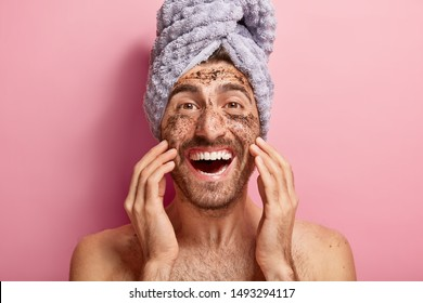 Male beauty concept. Happy joyous man applies coffee scrub on face, removes dark dotes, wants to look refreshed, has wrapped towel on head, poses against pink background topless, shows white teeth
