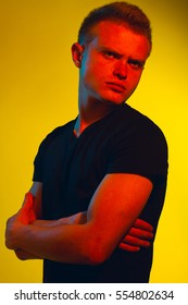 Male beauty concept. Pop-art portrait of young man with perfect haircut wearing black t-shirt over yellow background. Avant-garde, disco style. Close up. Studio shot