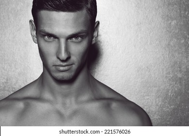 Male beauty concept. Portrait of fashionable and undressed young man with stylish haircut posing over gray background. Perfect hair & skin. Tough guy. Vogue style. Close up. Studio shot