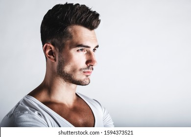 Male beauty concept. Portrait of handsome young man with stylish haircut posing over gray background. Perfect hair & skin. Close up. Studio shot
