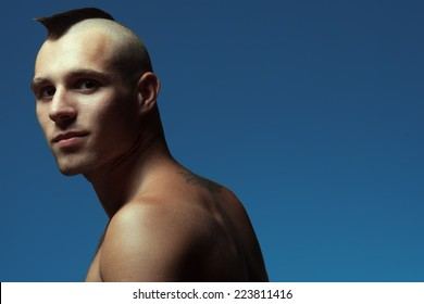 Male beauty concept. Portrait of handsome muscular male model posing over blue background. Shaved head with upright crest. Healthy skin, hairy chest. Tough guy style. Copy-space. Close up. Studio shot