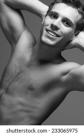Male beauty concept. Portrait of handsome muscular male model posing over gray background with hands up. White shiny smile and healthy clean skin. Close up. Studio shot