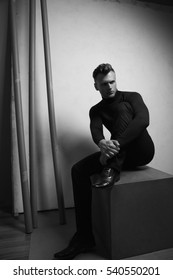 Male beauty concept. Portrait of handsome young man with stylish haircut wearing black clothes and sitting over light gray background. Street fashion style. Copy-space. Monochrome studio shot