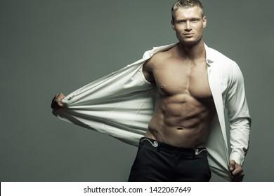 Männliche Schönheit, Modekonzept. Portrait des gut aussehenden männlichen Models in klassischem Hemd, Hosen auf grauem Hintergrund. Guy zeigt seinen perfekten Körper. Blondes Haar, gesunde, saubere Haut. Leerzeichen kopieren