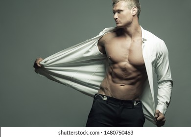 Male beauty, fashion concept. Portrait of handsome muscular male model in classic shirt, pants posing over gray background, showing his perfect body. Blond hair, clean skin. Copy-space. Studio shot