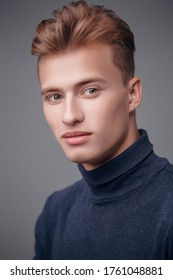 Male beauty, fashion. Portrait of a handsome young man with blond hair posing at studio on a gray background.