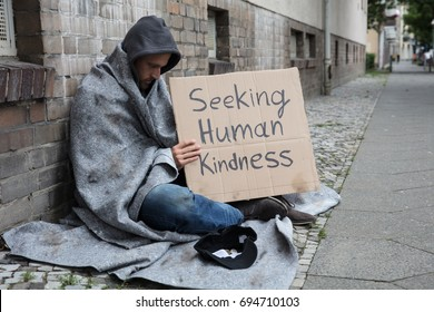 Male Beggar In Hood Showing Seeking Human Kindness Sign On Cardboard