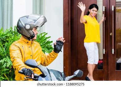 Male biker saying goodbye to her girlfriend standing at closed door