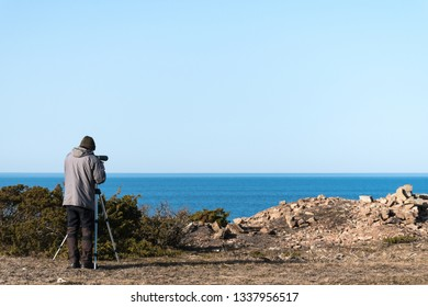 Male bird watcher by the coast of the swedish island Oland