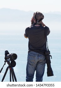 A male bird watcher taken from behind wearing a hat looks across sea to distant mountains with binoculars.A telescope and tripod are by his side- Image