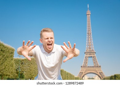 Male blogger human rights activist shows stop sign on migration of people to Europe, Eiffel Tower, Paris, France.