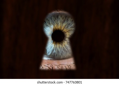 Male blue eye looking through the keyhole. The concept of voyeurism, curiosity, Stalker, surveillance and security