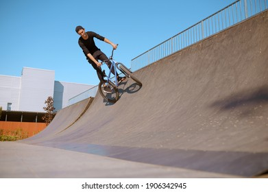 Male bmx rider doing trick on ramp in skatepark