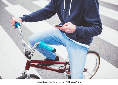 Male BMX rider on street with phone, walking on the zebra crossing