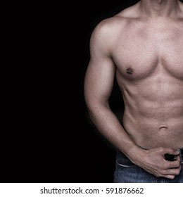 male body part with hand in belt and nipple piercing over a black background
