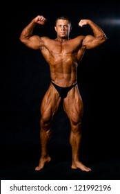 A male bodybuilder flexing his muscles. black background