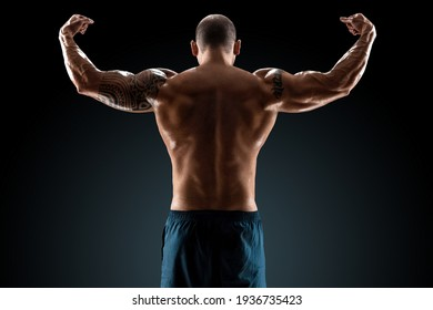 Male bodybuilder with light stubble and bare torso shows muscularity against a dark background. The concept of a fitness club, doing sports, weightlifting. Copy space