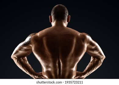 Male bodybuilder with light stubble with a naked torso posing against a dark background. The concept of a fitness club, doing sports, weightlifting. Copy space