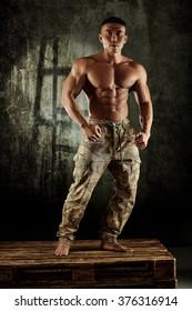 Male bodybuilder posing with bare chest in studio.