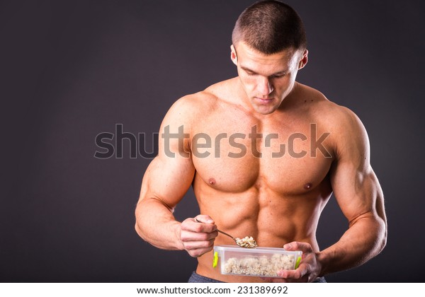Male bodybuilder posing on a dark background. Muscular man eating healthy food - rice. Man holding a tray with rice and eat with a fork. Rice, health, muscles, food - healthy eating concept.