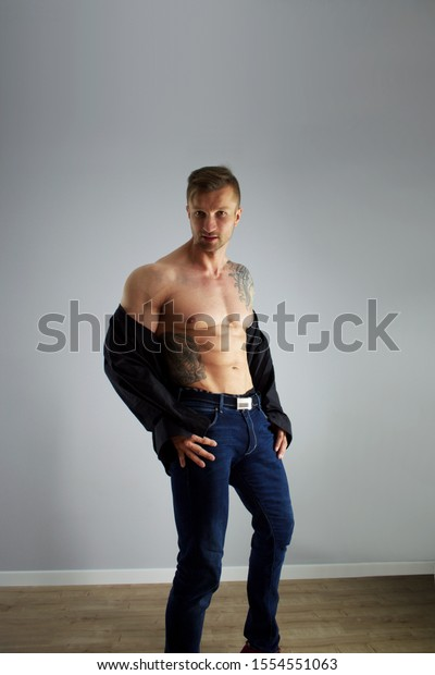 Male bodybuilder taking off his shirt revealing muscular torso, on light background