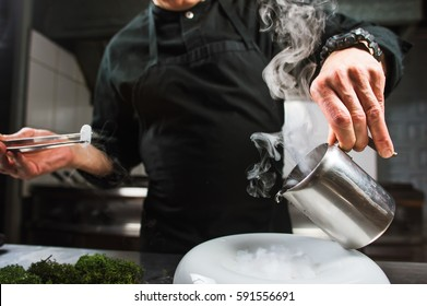 Male bold chef dressed in black is concentrated on cooking modern molecular dish with liquid nitrogen. Dark background. Molecular cuisine