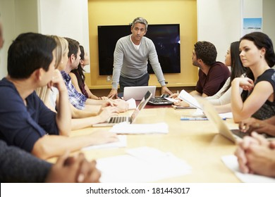 Male Boss Addressing Meeting Around Boardroom Table