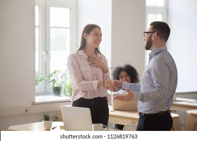 Male boss congratulating female employee handshaking and greeting her on special occasion, happy employer shaking hand of woman worker complimenting with promotion of good work results. Reward concept