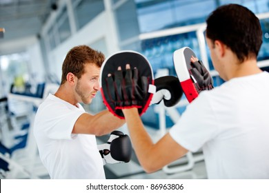 Male boxer at the gym with his trainer