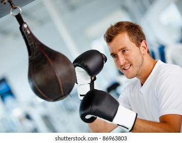 Male boxer at the gym hitting the punching ball