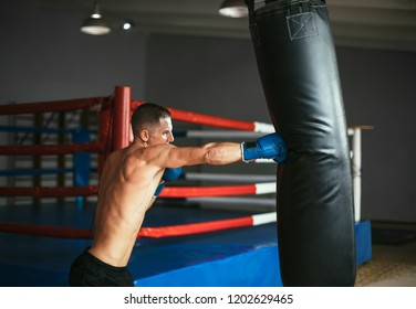 Male boxer hitting punching bag at a boxing studio. Sport training concept