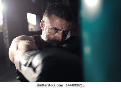 Male boxer punching a boxing bag in warehouse.