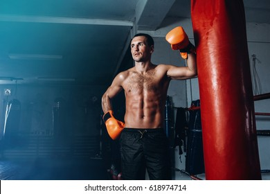 Male boxer training in dark gym. Strong Athletic Man Fitness Model Torso showing six pack abs. Portrait of boxer with gloves