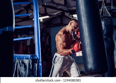 Male boxer training with punching bag in dark sports hall. Young boxer training on punching bag. Male boxer as exercise for the big fight. Boxer hits punching bag.