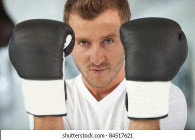 Male boxer wearing boxing gloves at the gym