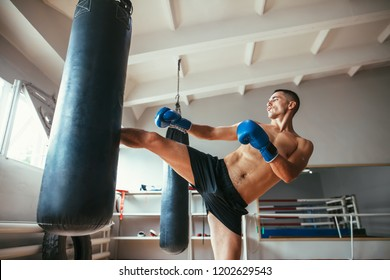 Male boxer workout high kick on the punching bag in gym. Sport concept