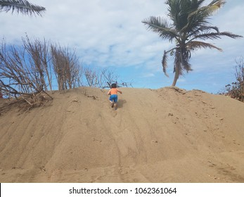male boy child climbing on sand dune on beach in Camuy Puerto Rico